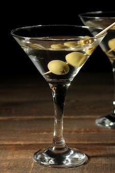 Martini dans un verre à vin en verre avec des olives vertes sur une brochette sur une table en bois marron. cocktails. bar