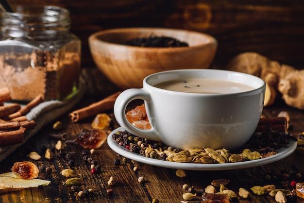 Masala chai dans une tasse blanche avec différentes épices