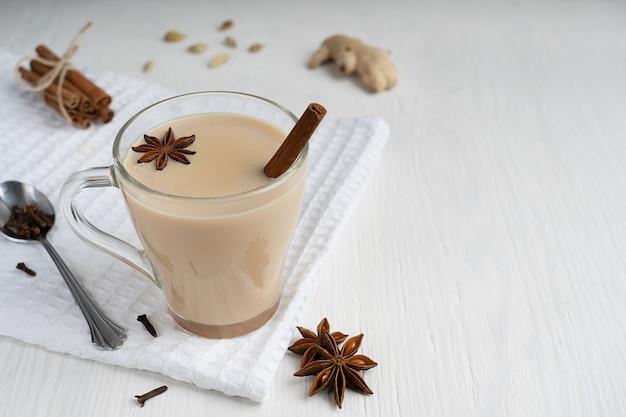 Masala chai indien ou thé aux épices mélangées avec anis, cannelle, gingembre et lait sur table en bois blanc