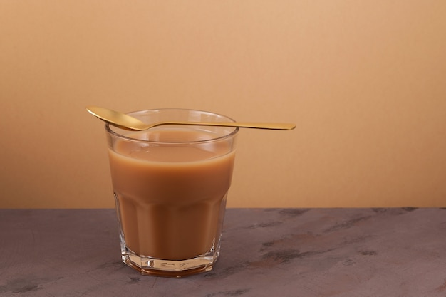 Masala chai ou thé karak sur fond marron. boisson épicée traditionnelle indienne.