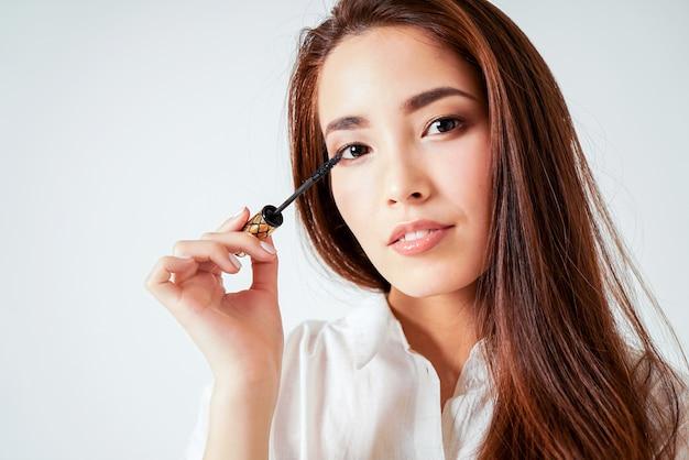 Mascara maquillage beauté jeune femme asiatique avec de longs cheveux noirs sur fond blanc