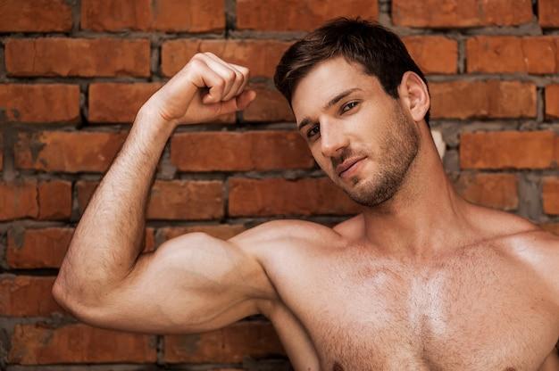 Masculinité. beau jeune homme musclé posant debout contre le mur de briques