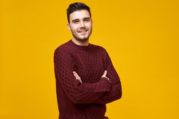 Masculinité, confiance et langage corporel. tir isolé du beau jeune homme joyeux en pull marron tricoté se sentant confiant et fier de lui-même, gardant les bras croisés sur sa poitrine, souriant