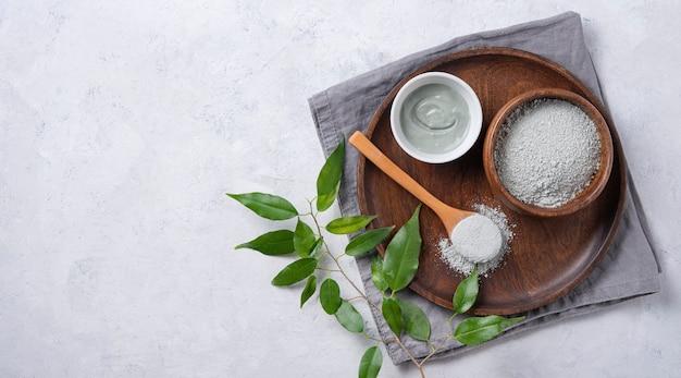 Masque en argile verte cosmétique à la maison dans un bol en bois sur un fond de béton gris