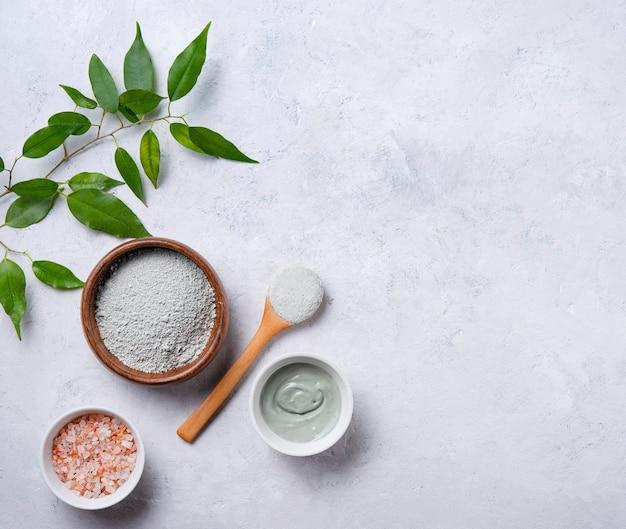 Masque en argile verte cosmétique à la maison dans un bol en bois et sel de mer rose sur fond de béton gris. mon propre cosmétologue