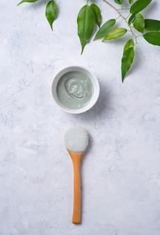 Masque en argile verte cosmétique à la maison sur un fond de béton gris