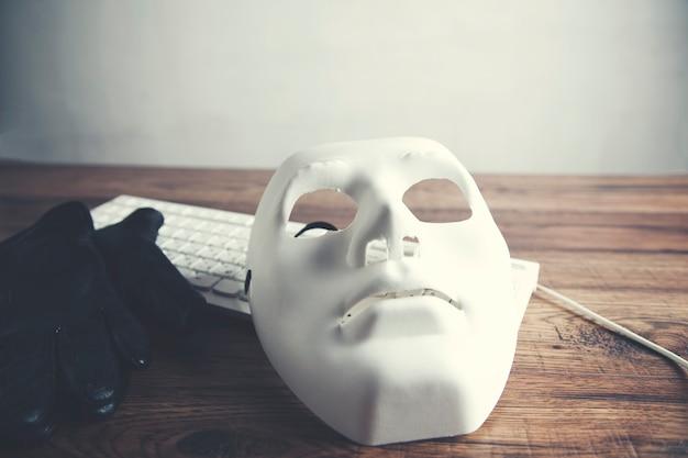 Masque blanc sur clavier d'ordinateur portable