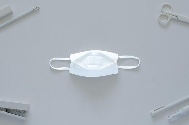 Masque blanc avec fournitures de papeterie scolaire et de bureau pour la rentrée scolaire et nouveau concept normal.