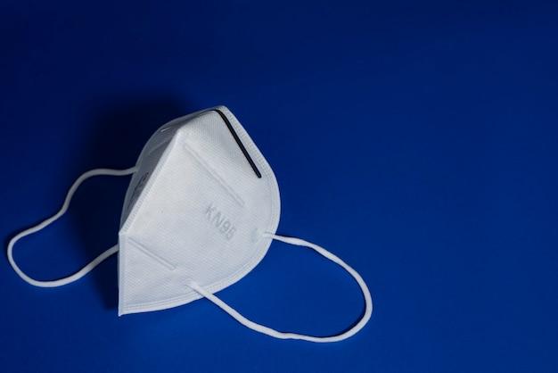 Masque blanc kn95 ou n95 avec masque médical antiviral pour la protection contre le coronavirus sur bleu