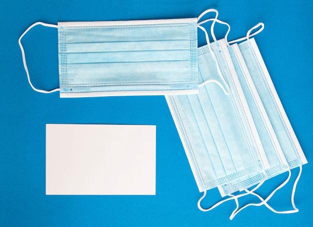 Masque bleu médical sur fond bleu et vue de dessus d'une feuille de papier blanche