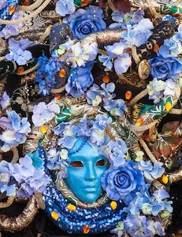 Masque bllue avec décorations florales exposées pendant le carnaval de venise