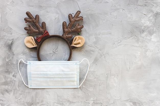 Masque buccal chirurgical blanc et bandeau de cerf de noël. quarantaine, verrouillage et coronavirus covid-19, célébration des vacances, éloignement social et concept de saison d'hiver