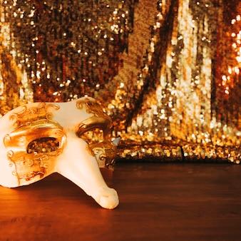 Masque de carnaval blanc vénitien sur table en bois contre tissu paillettes