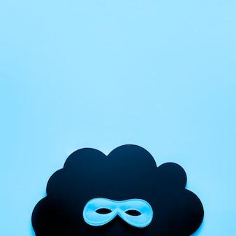 Masque de carnaval bleu sur nuage de papier noir avec espace copie