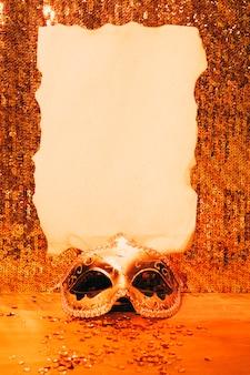 Masque de carnaval élégant avec du papier brûlé sur du tissu à paillettes brillant