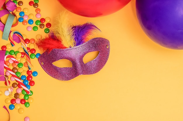 Masque de carnaval sur fond jaune avec mardi gras, carnaval vénitien, brésilien avec copie espace