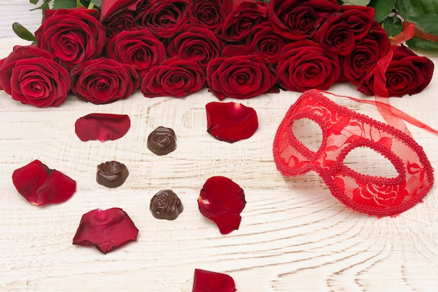 Masque de carnaval rouge, bouquet de roses rouges et chocolats sur bois clair.