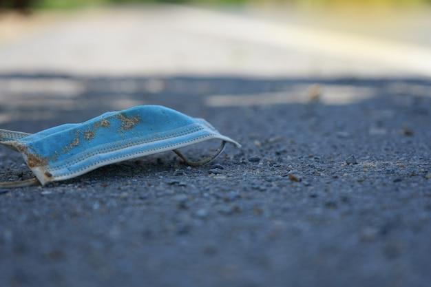 Masque chirurgical après usage tombé sur la route dangereux et sale dans la rue