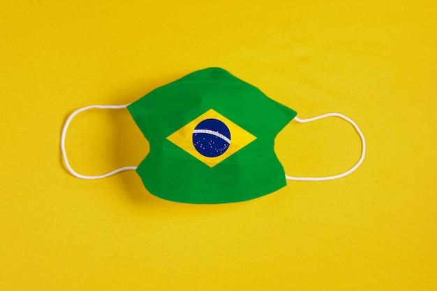 Masque chirurgical sur fond jaune avec drapeau brésilien