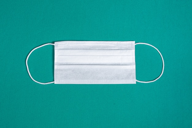 Masque chirurgical sur fond vert minimaliste