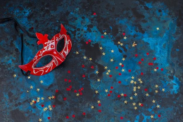 Masque, confettis sur fond bleu