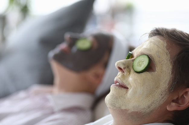 Un masque cosmétique a été appliqué sur les visages masculins et féminins et des tranches de concombre sur les yeux.