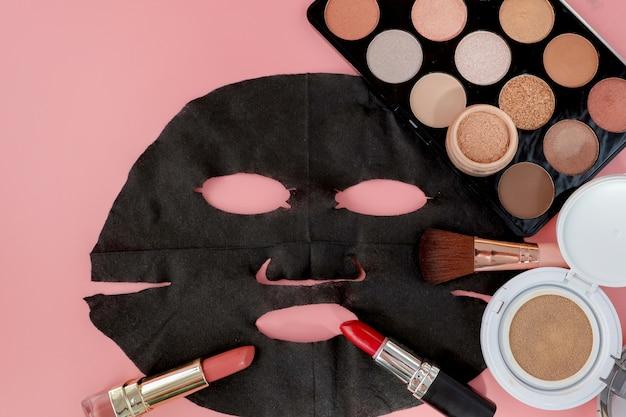 Masque cosmétique noir et maquillage sur fond rose avec espace copie