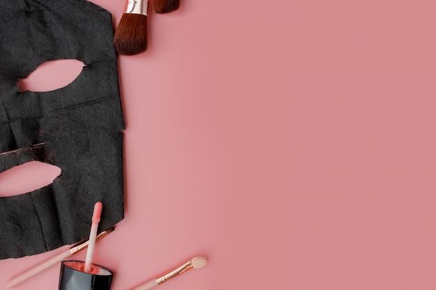 Masque cosmétique noir et maquillage sur fond rose
