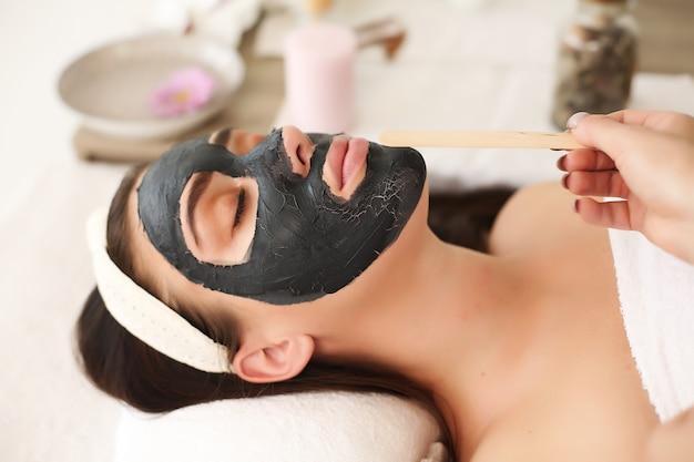 Masque cosmétique sur le visage, brune faisant des traitements au spa