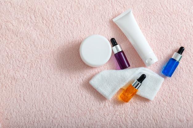 Masque crème hydratant à l'huile de sérum tampons de coton cosmétiques de soins de la peau pour la maison ou le salon cosmétiques de soins d'esthéticienne pour spa de cosmétologie de la peau ou utilisation quotidienne vue de dessus sur une serviette rose avec espace de copie