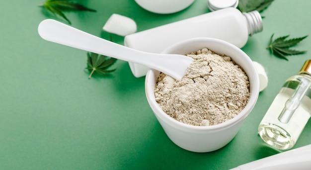 Masque facial en argile avec du cannabis cbd infusé et mis en cosmétiques de soins de la peau dans un tube blanc avec de l'huile de cbd, sérum dans un compte-gouttes, longue bannière web de feuille de cannabis sur fond vert.