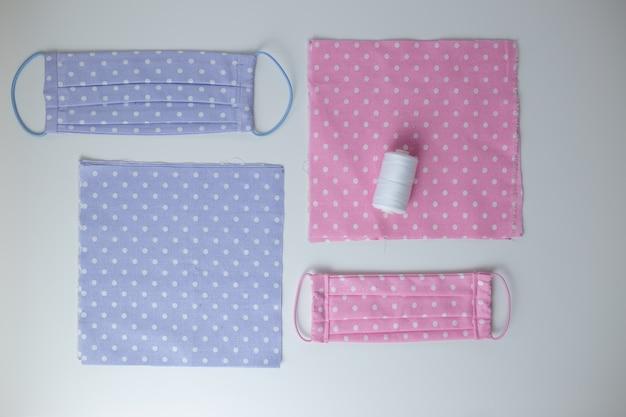 Masque facial contre les virus à la main, cousez un masque de protection, des morceaux de tissu en pointillé, des fils sur un tableau blanc. mise à plat avec un tissu rose et bleu, des ciseaux et des fils.