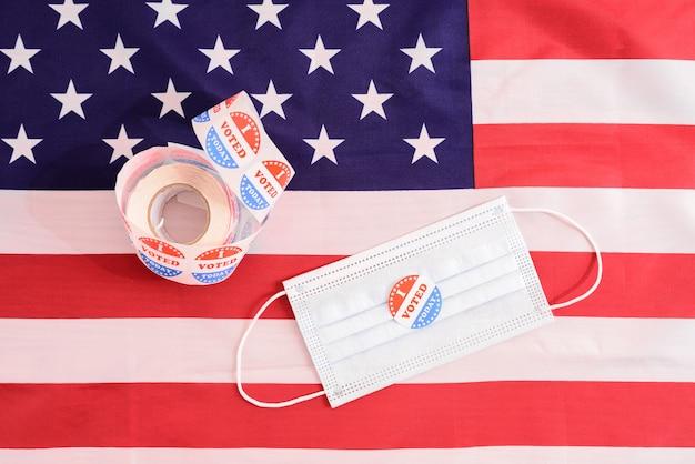 Masque facial d'un fier électeur lors des élections démocratiques aux etats-unis avec des autocollants sur le drapeau américain patriotique.
