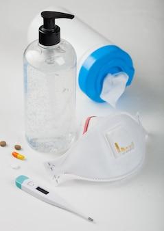Masque facial avec gel désinfectant, lingettes alcoolisées sur blanc avec thermomètre et pilules. meilleure protection contre les coronavirus, les germes, les bactéries et les virus.