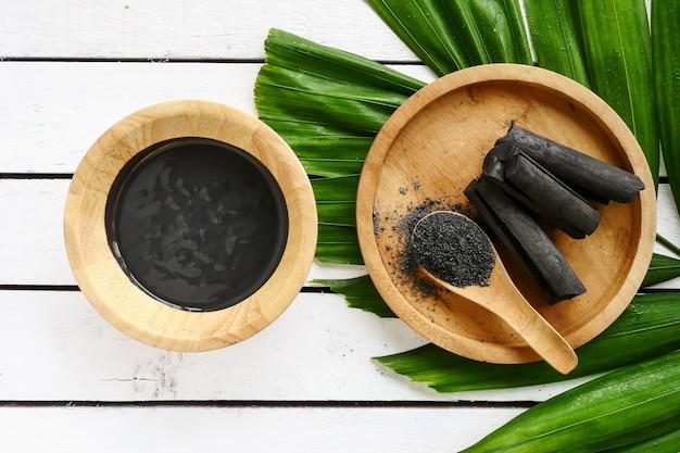 Masque facial et gommage au charbon actif en poudre sur table en bois