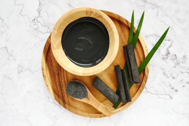 Masque facial et gommage au charbon actif en poudre sur une table en marbre