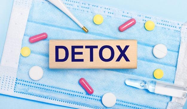 Sur un masque facial jetable bleu clair, il y a des comprimés, un thermomètre, une ampoule et un bloc de bois avec le texte detox. notion médicale