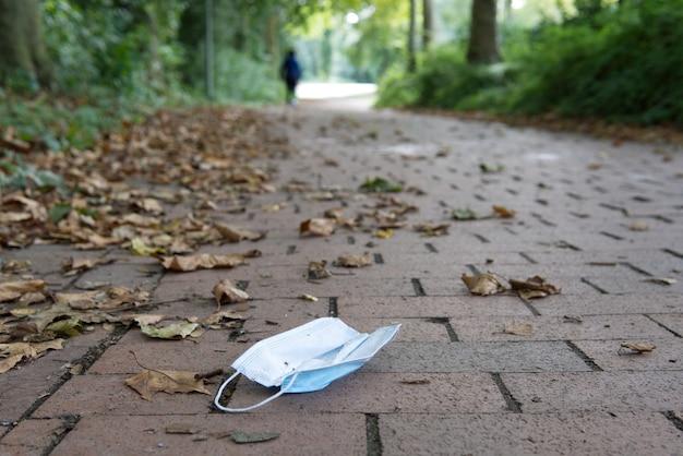 Masque facial jeté sur le trottoir et arrière-plan flou