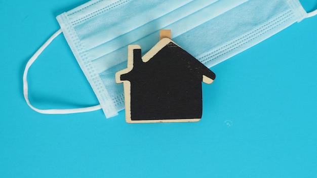 Masque facial ou masque médical et petit panneau d'accueil en bois noir sur fond noir.