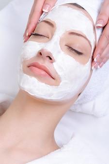 Masque facial pour jeune femme dans le salon de gros plan de beauté