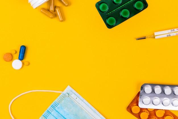 Masque facial de protection médicale en coton bleu sur fond de papier jaune avec des pilules. maladie du coronavirus. concept de virus corona. concept de soins de santé et médical.