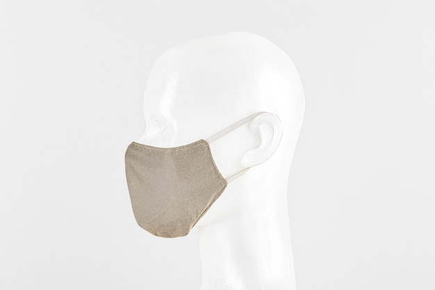 Masque facial en tissu beige sur une tête factice