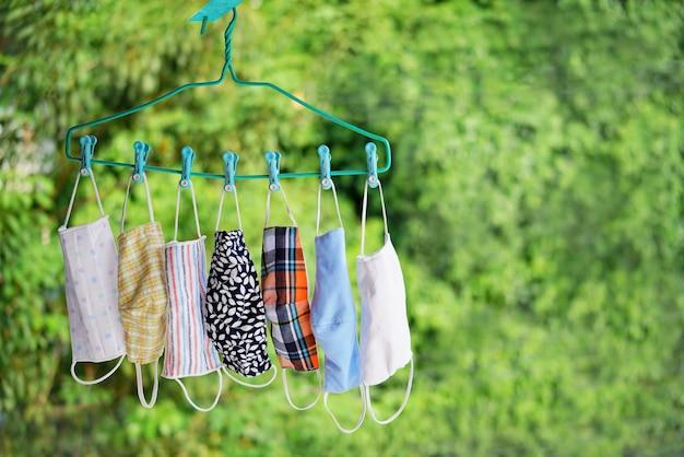 Masque facial en tissu coloré, lavable et suspendu à un cintre pour réutilisation sur fond vert extérieur.