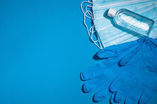 Masque de gants médicaux et gel d'alcool pour protéger l'infection pendant la pandémie de coronavirus vue de dessus sur bleu clair avec copie espace