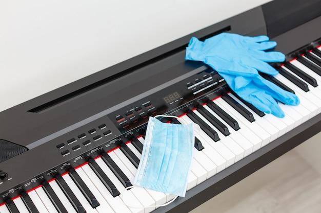 Un masque et des gants de protection contre les virus se trouvent sur le piano