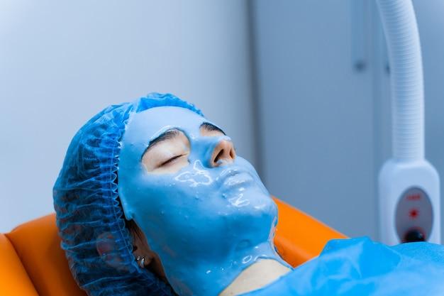 Masque hydratant à l'alginate pour le visage et la peau de la jeune fille. procédure de spa pour le rajeunissement. esthéticienne frotte le masque bleu. dermatologie en clinique médicale