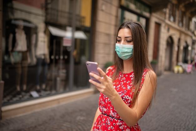Masqué jeune femme marchant dans une ville tout en utilisant son téléphone portable