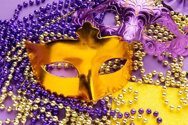 Masque de luxe doré et collier de perles violettes