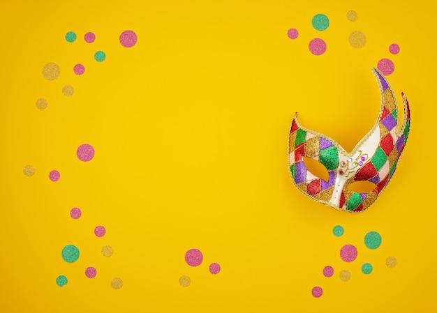 Masque de mardi gras ou de carnaval festif et coloré et accessoires sur mur jaune. mise à plat, vue de dessus, espace copie