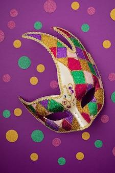 Masque de mardi gras ou de carnaval festif et coloré et accessoires sur un mur violet. mise à plat, vue de dessus, espace copie